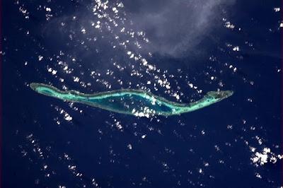 sebuah pulau ketika terlihat dari atas awan