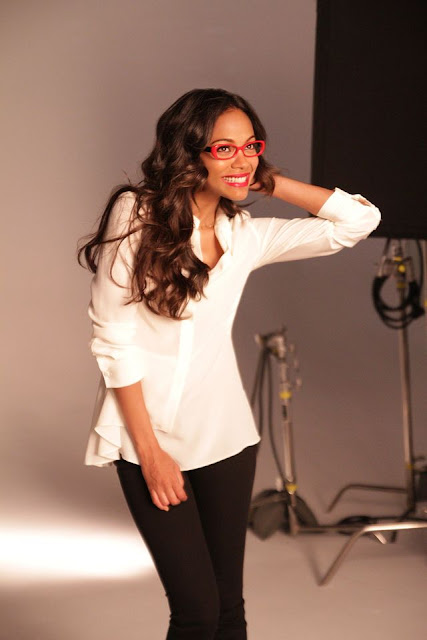 Actress Zoe Saldana models red glasses wearing a white shirt and black trousers