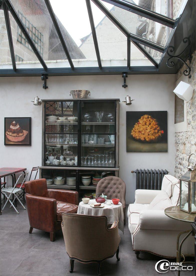 Coin salon cosy de la maison d'hôtes 'Le Cottage' avec un vaisselier 'Fancy' encadré de toiles de Philippe Brosse
