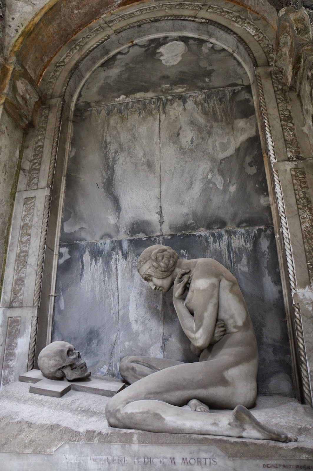 Beautiful stone statuary in the Staglieno Cemetery in Genoa Italy - lady with skull and cross