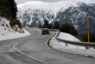 Coche circulando por carretera nevada