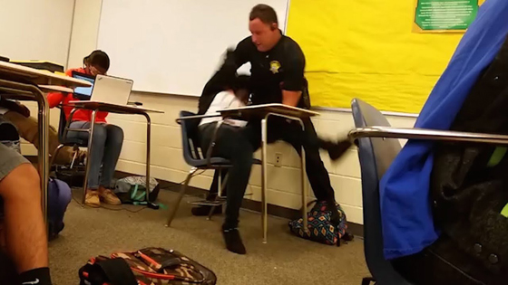 "A ""police officer"" launches an attack on a female student (while a student seated behind her shields her eyes from the terror). The student under full frontal assault ""refused to follow the teachers instructions"" and was flipped, thrown, dragged and then arrested. She now has a criminal record to contend with for the rest of her life — for acting up in class."