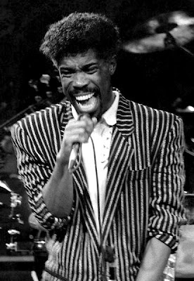 pop star Billy Ocean sings on stage in New York, in a stripy jacket