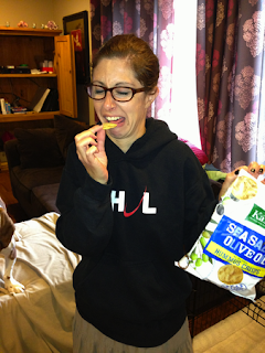 Woman making a grimacing face while trying to eat an unpleasant tasting chip