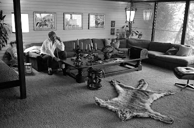 McQueen takes a call in the living room of his eclectic home in Hollywood, 1963