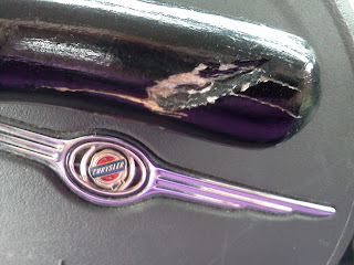 The end of a black cane, damaged and cracked, set against the steering wheel of a PT Cruiser