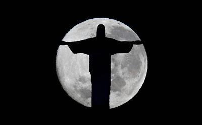 A imagem mostra uma enorme lua cheia atrás com a estátua do Cristo Redentor à frente