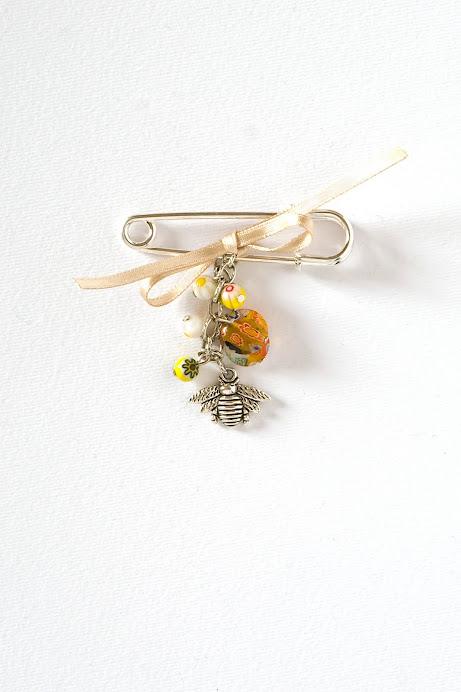 Spilla con decoro: ape in argentone, nastro raso e perle di murrina.