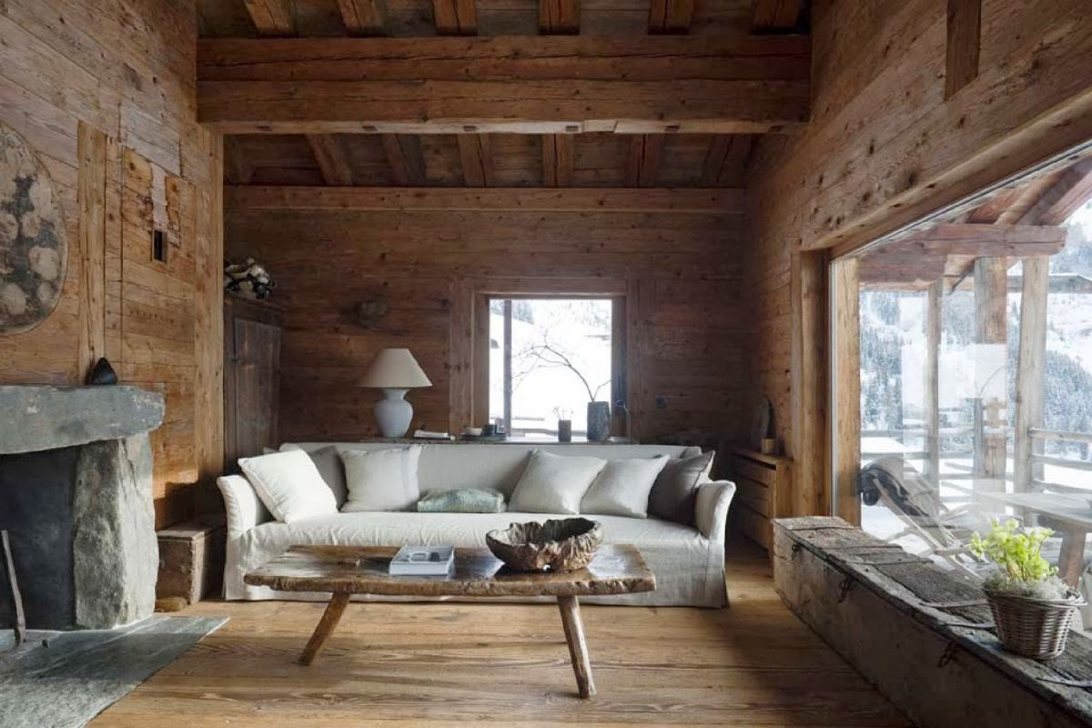 Fully wood paneled mountain home living room with stone slab fireplace and window seat