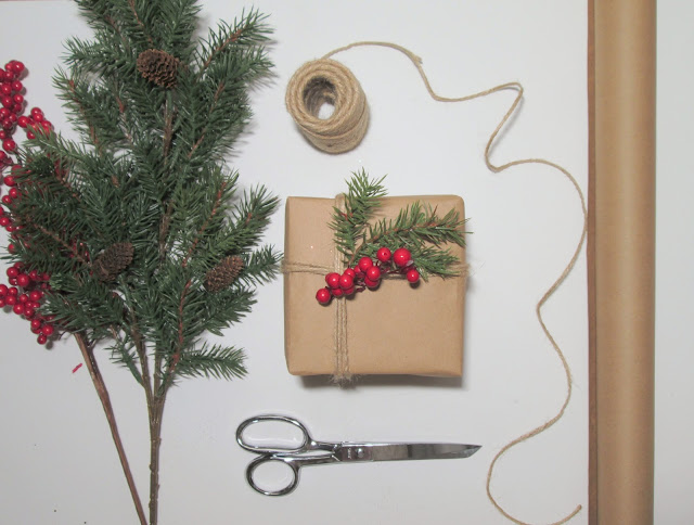 Christmas gift wrapping with tree sprigs, striped ribbon, berries, twine and brown paper