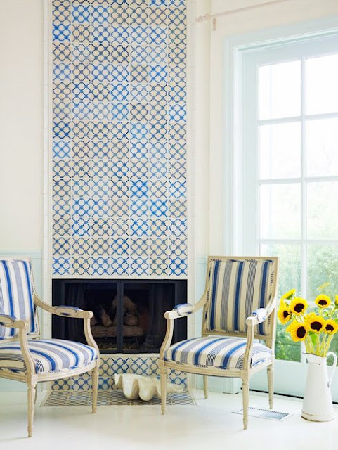 Living room with fireplace covered in blue, white and yellow antique Portuguese tiles, with two upholstered blue and white striped chairs