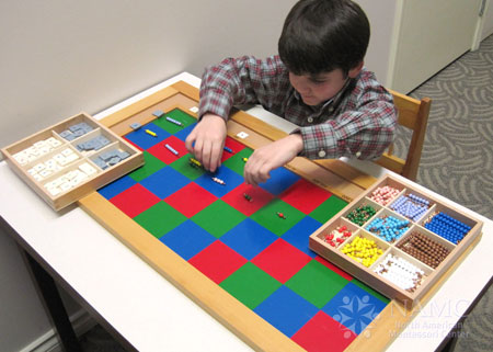 NAMC montessori math favorite lower elementary material checkerboard boy doing big math