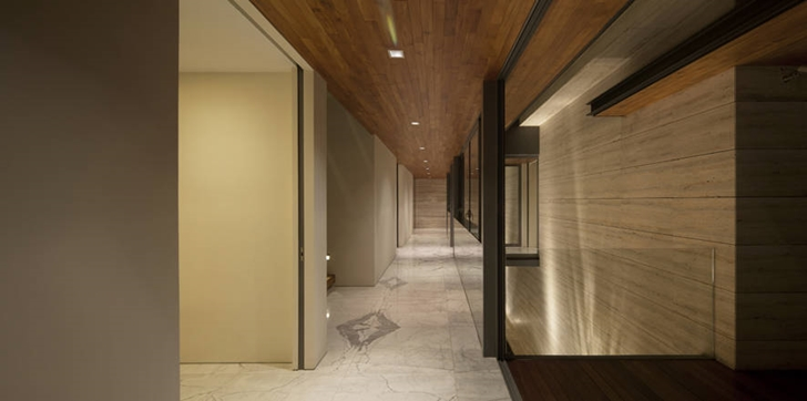 Hallway of Travertine Dream House by Wallflower Architecture + Design at night