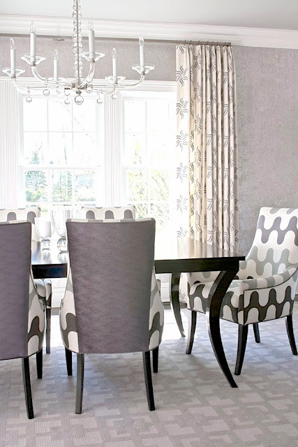 Grey dining room with graphic print upholstered chairs and carpeting
