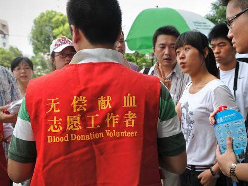 Voluntário orienta chineses em posto de doação de sangue (Foto: AFP)