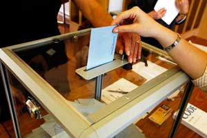 Persona dipositando una papeleta en una urna durante unas elecciones