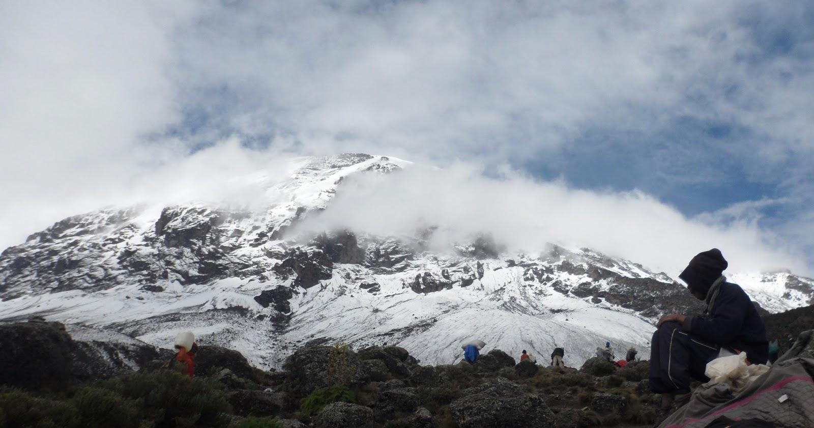 Porteador-frente-vistas-cima-Kilimanjaro-desde-campamento-Karanga