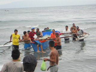 folks begin to lift boat onto shore