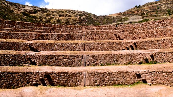 One of the most visually stunning Inca ruins is at Moray, an archaeological site in Peru approximately 50 km northwest of Cuzco and just west of the village of Maras. In a large bowl-like depression, is constructed a series of concentric terraces that looks like an ancient Greek amphitheater. The largest of these terraces are at the center – they are enormous in size, and descend to a depth of approximately 150 meter, leading to a circular bottom so well drained that it never completely floods, no matter how plentiful the rain.
