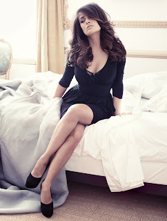Salma Hayek elegant in black dress and heels sitting on a bed