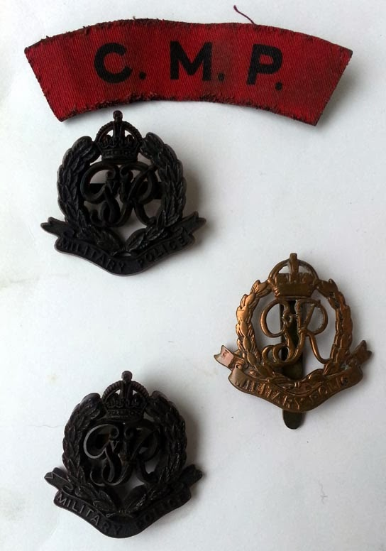 A red cloth shoulder flash with letter C.M.P. and two brown plastic badges and a brass badge all with GVIR in the centre of a wreath, crown above, Military Police in a scroll below