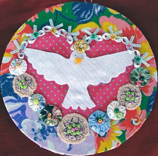 """Foto de enfeite caipira de """"Espírito Santo"""" de feltro, centralizado dentro de um coração de fitas, crochês e fuxicos, num círculo de tecido de chita florido"""
