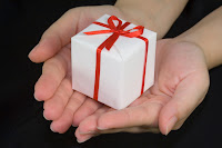small white gift with red bow held out in two hands with palms up