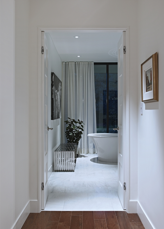 Picture of modern bathroom as seen through the doors from the hallway