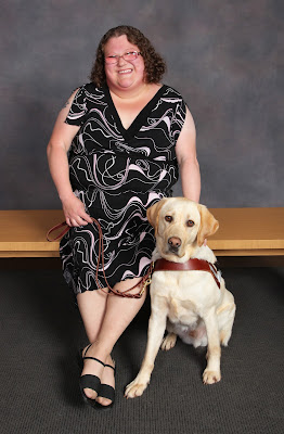 Deana's official GDB graduation photo smiling while posing with her guide dog Mambo (yellow Lab in harness).