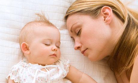 woman sleeping-with-baby-خطورة لمس رأس الاطفال حديثي الولادة