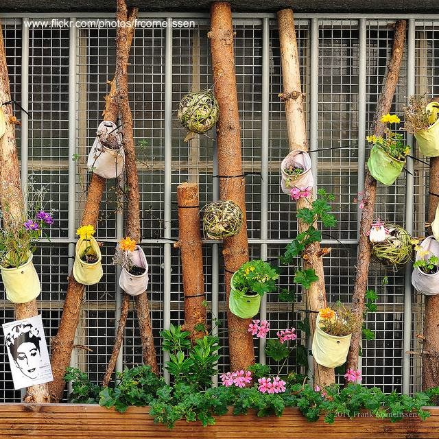 Ventana decorada con cañas y maceteros del lado exterior