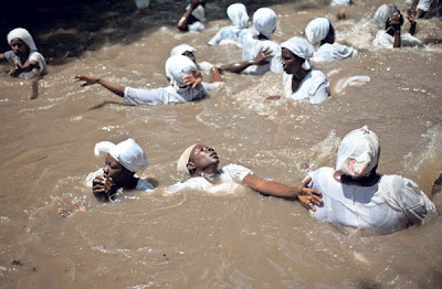 BEBERAPA pengamal voodoo mandi di sebuah kolam yang dianggap suci di Souvenance, Haiti.