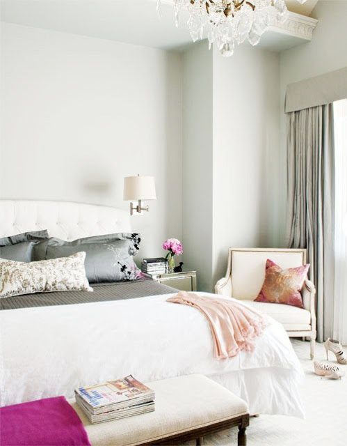 Bedroom with grey walls, an ottoman at the foot of the bed, a nightstand with a wall mounted light and an armchair