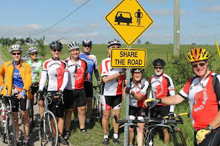image Kawartha Cycling Club June Share the Road Campaign Kick-Off shows cycists with bicycles around a newly erected Share the Road sign