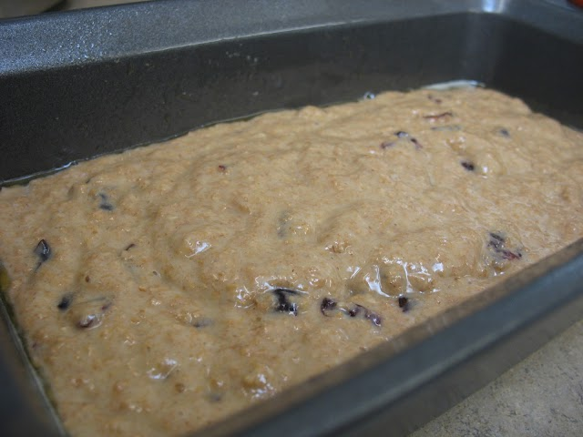 Muffin mixture with cranberries poured into loaf pan.