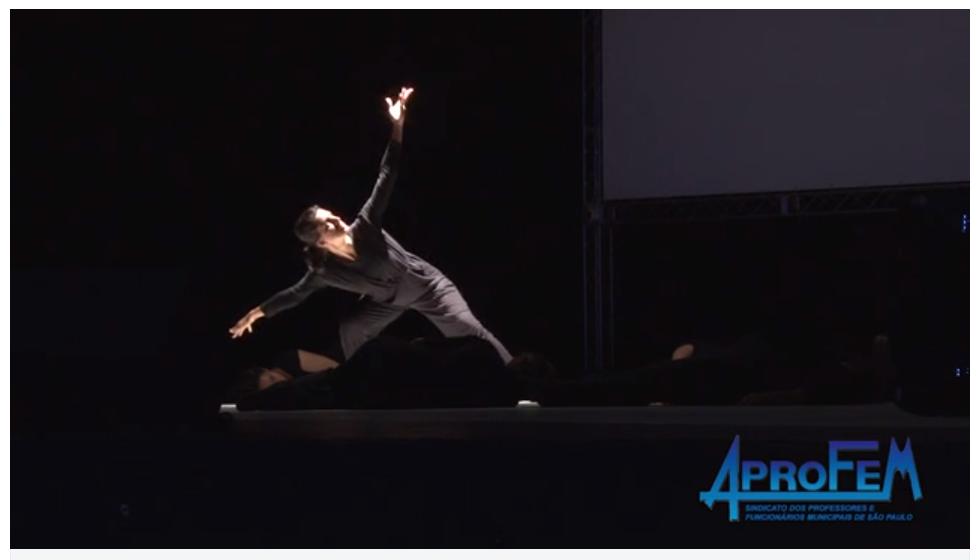 Descrição da Foto: Intérprete está com as pernas abertas lado-a-lado, com um braço para baixo o outro esticado para cima, formando uma curva com os braços e tronco sobre um foco de luz branca.