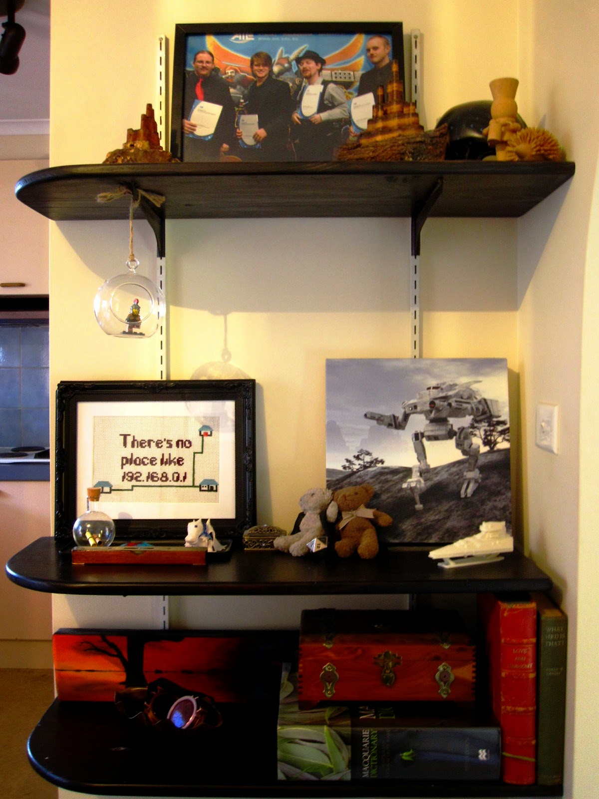 A set of three wall shelves showcasing a selection of personal items including a photograph, books, a 3D-printed space ship and two small teddy bears.