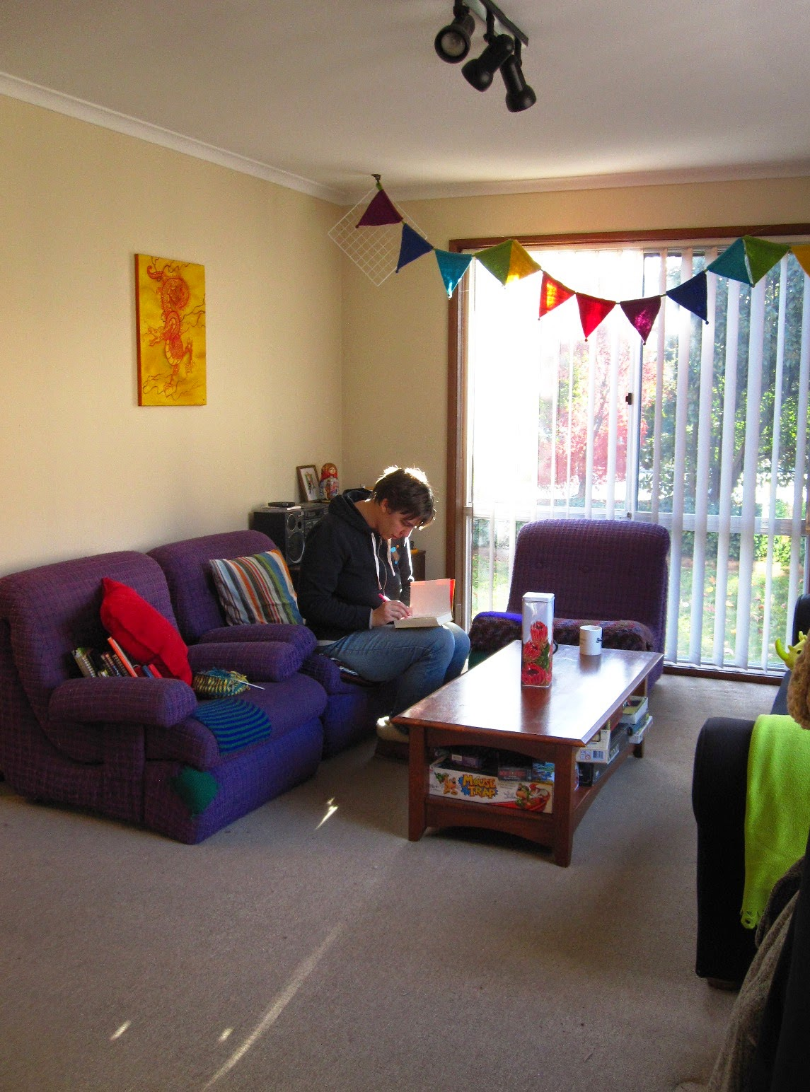 Lounge with colourful felted bunting, three purple lounge chairs with bright cushions and a wooden coffee table. A woman sits on one of the chairs writing in a note book.