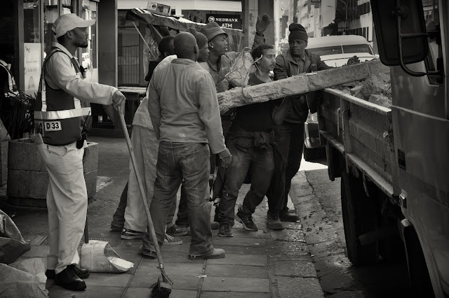 Labourers load a truck with concrete in this street photograph from Cape Town South Africa