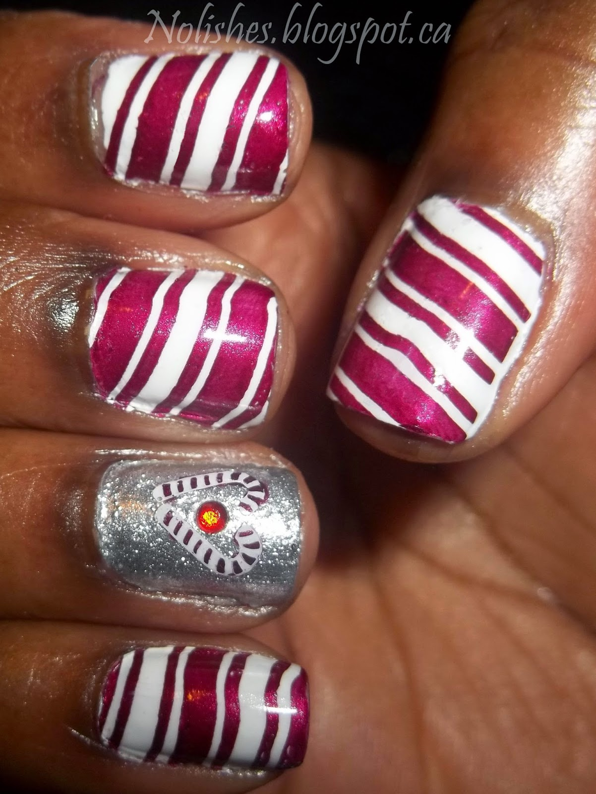 Nail stamping manicure featuring red and white striped nails, and ring finger accent nail with sparkly silver base colour, with 2 candy canes arranged in a heart shape, with a red nail art rhinestone in the centre of the candy-cane heart.