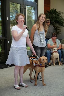 Rue on stage at graduation with her new handler and Amber next to them
