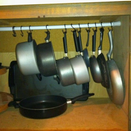 Pots and pans hanging by curtain rod inside cupboard