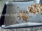 Prajitura Deliciu cu crema si biscuiti Preparare blat - asezam nuca maruntita in tava