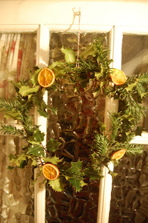 Christmas wreath made from holly, yew and dried oranges.