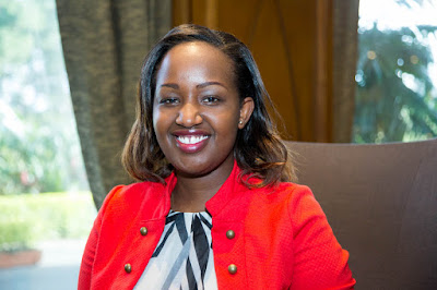 Portrait photo of Carol Wanjiku, seated and smiling, wearing a red jacket
