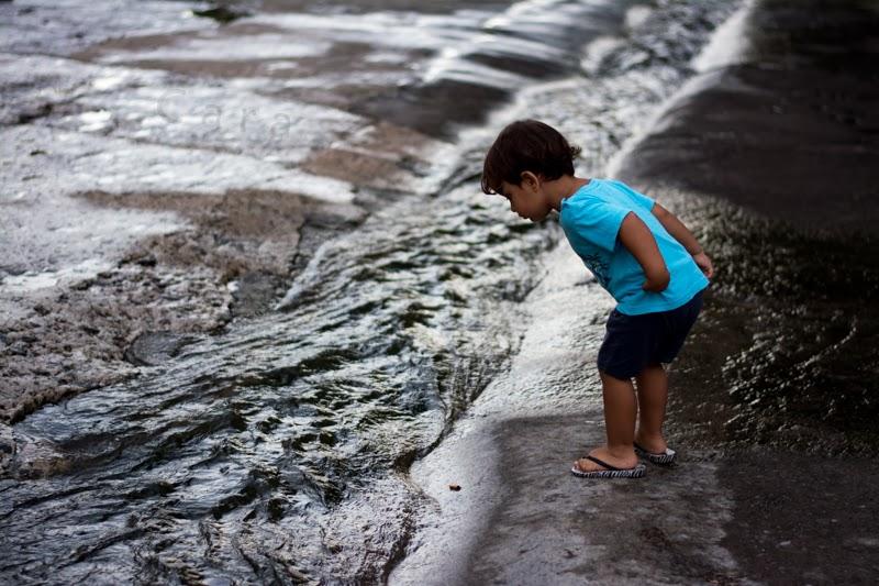 Petit garçon regarde couler l'eau dans un canal