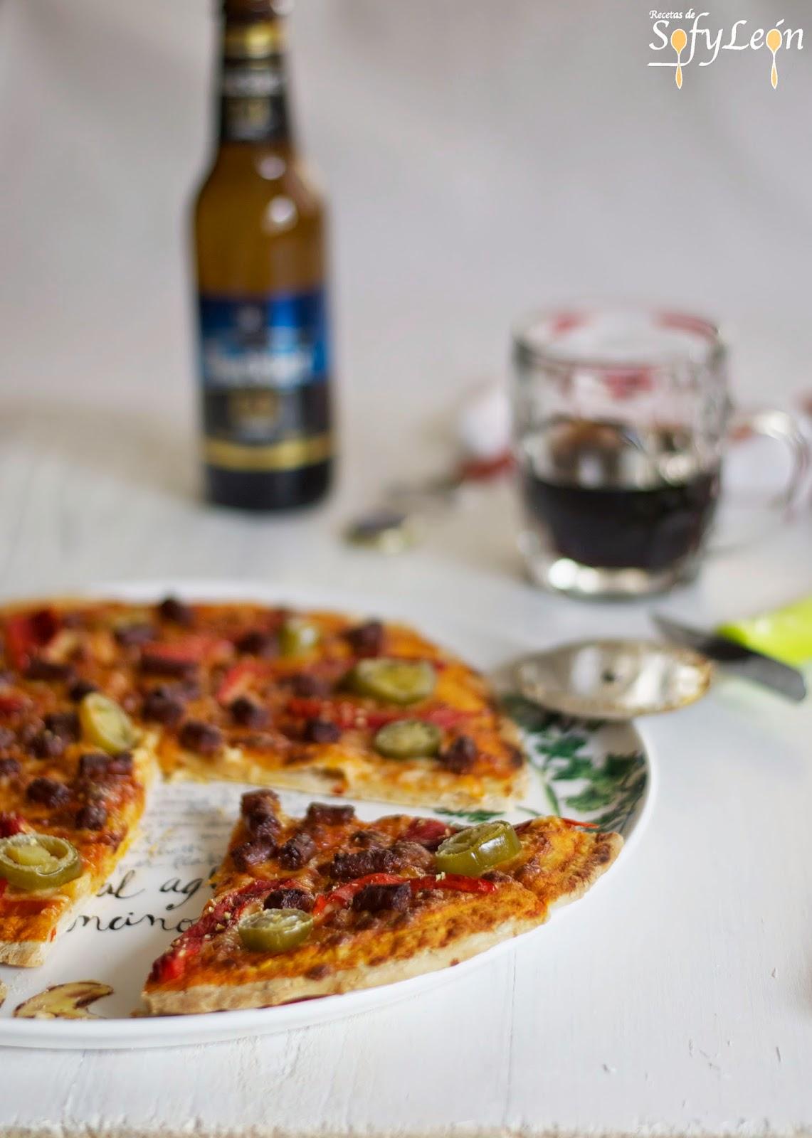 Primer plano de pizza con chorizo y jalapeños.