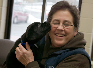 A small black lab puppy is licking the cheek of a woman wearing glasses, with dark, short hair. She is smiling with her eyes closed. She is wearing a brown hooded sweatshirt with a blue vest.