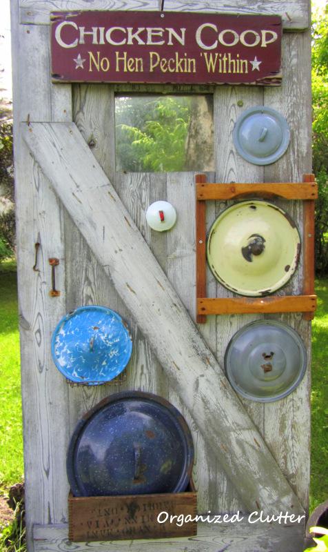 Garden Junk Decor: Lids on a Barn Door www.organizedclutterqueen.blogspot.com