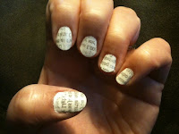 womens fingernails covered in newspaper